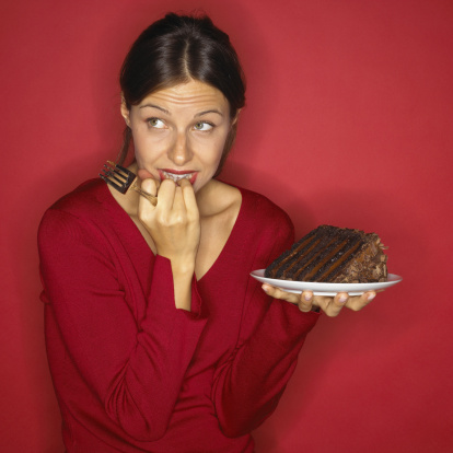 conflicted-woman-holding-chocolate-cake-gettyimages